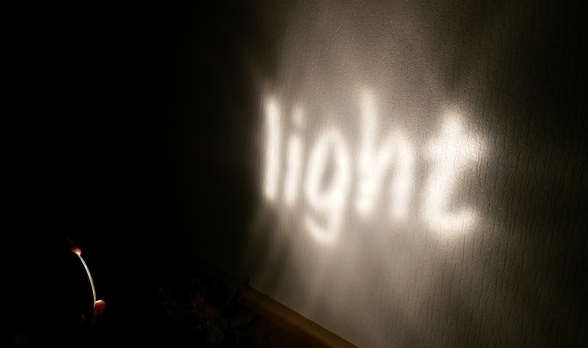 Project Image of Physionary Facet Lenses showing projected 'LIGHT' typography