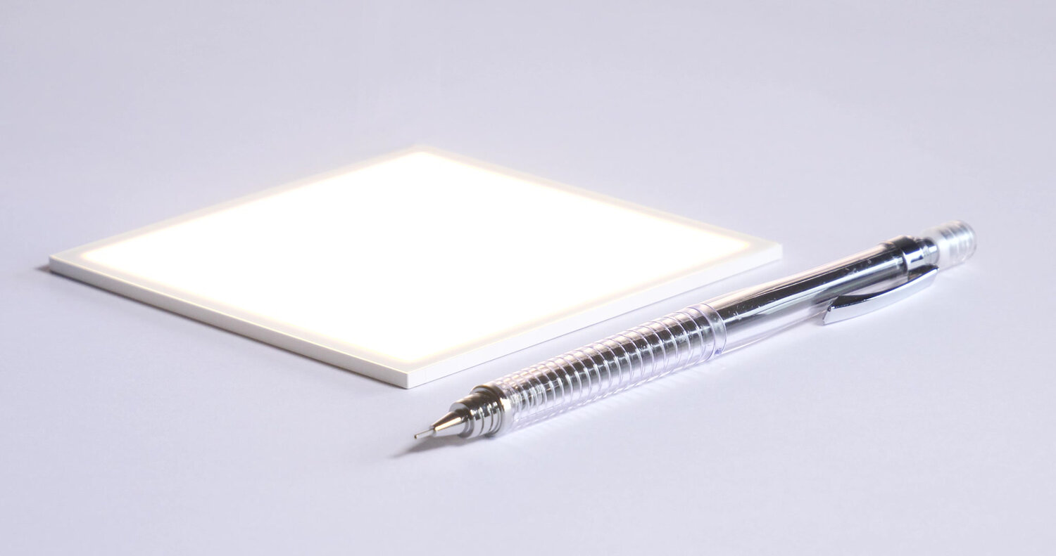 Image of Hikari SQ and a pen to demonstrate the size and flatness of the novel lighting solution